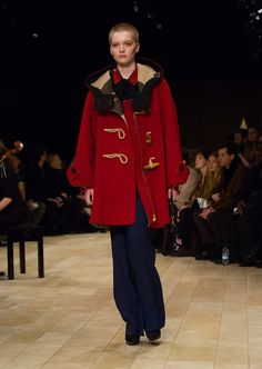 Military red oversize duffle coat worn over tailored boot-leg trousers and a knitted merino wool polo shirt