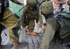 Photos show a group of Israeli occupation soldiers kicking Palestinian , and another pinning him down to the ground with his knee. Military says the man was resisting arrest, but that the incident is being investigated.