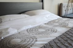 A collection of embroidered cotton bedding, including pillowcases and duvet covers, in soft white cotton with a contemporary grey embroidered design.