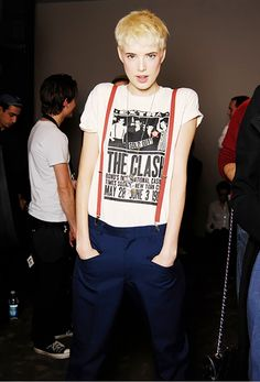 Agyness Deyn wearing a graphic tee, navy trousers, and red suspenders