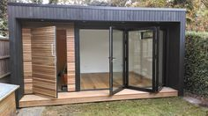 Garden room with contrasting cedar cladding and bi-fold doors and decking
