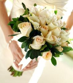 Classic cream bouquet of ivory calla lilies and small ivory roses.