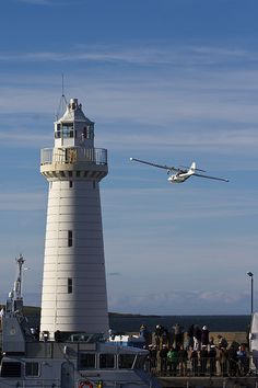 Armed Forces Day 2014 (Newtownards Airfield). Consolidated Catalina G-PBYA flys past Donaghadee Lighthouse, County Down, Northern Ireland.