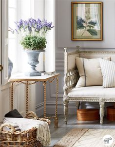 Potted lavender, antique gilded accents and rough-hewn linen upholstery and accent pillows make for a chic French country living room.