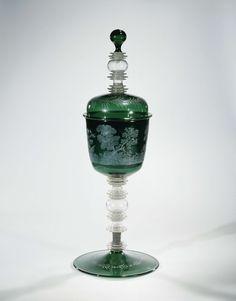 Anonymous | Lidded wine glass, Anonymous, Hans Wolfgang Schmidt, c. 1675 - c. 1699 | Groene, conische voet. De stam samengesteld uit een holle knoop tussen vijf samengestelde schijven. Tussen de twee onderste schijven bevindt zich een zilveren montuur. Conische, groene kelk met afgeronde bodem. Gewelfd, groen deksel met een knop, bestaande uit een holle knoop en drie samengestelde schijven, eindigend in een groene bol. Op de kelk, in een doorlopend boslandschap, zwijnenjacht met twee jagers…