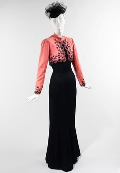 Ensemble Elsa Schiaparelli Spring/Summer 1940 Designed for Schiaparelli's summer 1940 collection, this jacket was worn with a black mermaid dress and a jet beaded black tulle hat. In sophisticated pink twill trimmed with contrasting black Spanish-influenced embroidery, the jacket exudes a certain chic that would be increased as worn by Millicent Rogers, the original owner. This design was well-received by the fashion press, particularly the mermaid dress, Schiaparelli's newest silhouette for