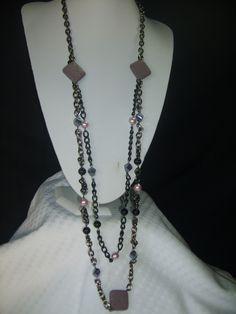 Moderno collar casual de dos vueltas, la primera de 55 cm. de largo y la segunda de 60 cm. elaborado con cubos de cristal austriaco, perlas de cristal, rombos de piedra volcánica, y ganchos de plata.