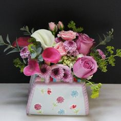 MOTHER'S GARDEN:  This cute ceramic purse is filled to the brim with flowers. Pink and white mini callas, roses, and spray roses are perfect to compliment each other.  #MatlackFlorist