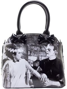 ROCK REBEL WE BELONG DEAD TOTE HANDBAG - We can't get enough of Frankenstein's Monster and his lovely Bride!  This vegan friendly tote features decorative bows that adorn the front and has studded details, rolled handles, and a removable shoulder strap.  This zip top bag is completely lined and also has a zip interior pocket, 2 open pockets, a great little easy access zip pocket on the back and 4 metal feet to keep this bag from getting damaged when set down.