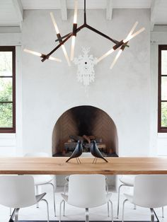 simple rustic white palette +fireplace alcove + bronze chandelier + wood table + modern chairs