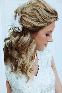Allover curls take on a vintage vibe with a feather and pearl-encrusted clip.