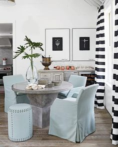 Tracery Interiors - Chic cottage dining room features a round concrete dining…