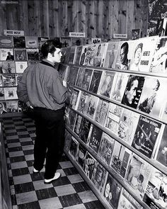 Pictured here is Elvis Presley, also known as 'The King' wandering a record store in Memphis, Tennessee. Elvis moved to Memphis with his family when he was old, it's where he began his music career in 1954 and really came into his own. The Addams Family, Musica Elvis Presley, Elvis Presley Photos, Mamie Van Doren, Fred Flintstone, Fred Astaire, Roger Daltrey, Lets Dance, Jimi Hendrix