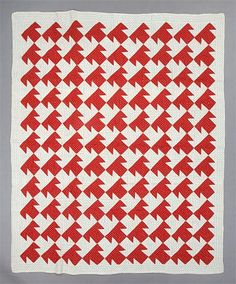 Mixed T quilt, cotton, machine pieced, hand pieced, red triangles set to create T shape on white ground - produces overall effect of interlocking, alternating red T's and white T's going in opposite directions; quilted in outline, double cable and diagonal line designs; backing is a plaid fabric, 198.5 x 162.5cm