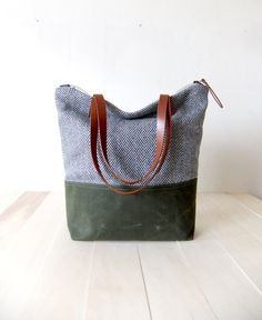 This is a perfect tote bag for everyday use. It has a waxed canvas base in olive green. Upper part is from herringbone tweed in grey. Straps are vegetable tanned leather in brown. Lining is made from natural durable soft cotton fabric. It has two interior pockets. I think it has a modern, casual, cozy style. This is also great as a gift! Fast International Shipping: Delivery in 2-5 days to the US, Canada, Australia and Europe; in 3-7 days to rest of the world! Measurements: 40x40x12 cm ...