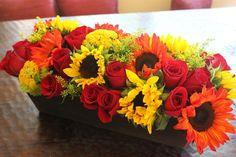 Rectangular Arrangement with over three dozen premium flowers.  Red freedom roses, orange & yellow sunflowers.