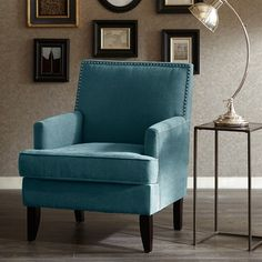 This track arm club chair with its sleek contemporary lines, exposed wood legs and added touch of individual nail head trim, gives it a charming new spin for a classic living room. Some assembly required.