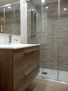 Los revestimientos cerámicos y el mueble del lavabo con columna auxiliar de madera son los puntos fuertes de esta reforma de baño pequeño con ducha.