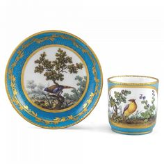 A SÈVRES CUP AND SAUCER 1764 decorated with a turquoise  bleu céleste  ground gilded with an  oeil de perdrix  pattern reserved with exotic birds in landscapes painted by Aloncle,  slight wear   Quantity: 2 interlaced Ls enclosing dateletter L for 1764, painter's mark of a scrolling N for François-Joseph Aloncle, saucer with incised reversed S, Wilfrid Evill Collection Label cup 6.1cm., 2½in., saucer 11.9cm., 4¾in.