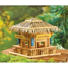 """Beachcombing birdies will belly up to this adorable wood snack shack! Just like a favorite seaside hangout, complete with straw roof, signs and """"barstool"""" perches. Item weight: 2 lbs. 8 1/4 x 8 1/4 x 7 3/4 high. Wood."""