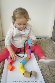 Toddler threading using large cardboard tubes