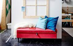 Foto van een zitplek bij het raam met kussens en een deken erop