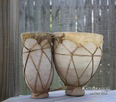 This set of ceramic djembe drums, made of a light tan neutral ceramic, are perfect for display at home or office. The sheep skin and strapping are original and in fair / good condition. The body has scuffs and a few chips adding to the vintage look of this piece. The dark spot in photo 4 is part of the hide and is not a hole. A personal favorite from my Etsy shop https://www.etsy.com/listing/454349890/vintage-ceramic-djembe-drums-congo-drums