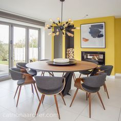Modern dining room with fireplace and bifold doors. This large 8 seater round dining table was complimented with dark curved wood and grey upholstered chairs. The sputnik ceiling light and yellow accent wall adds drama. Dining Room Fireplace, Dining Room Paint, Dining Room Wall Decor, Yellow Dining Room, Gray Dining Chairs, Round Dining Tables, Room Chairs, Accent Chairs, Dining Room Colour Schemes