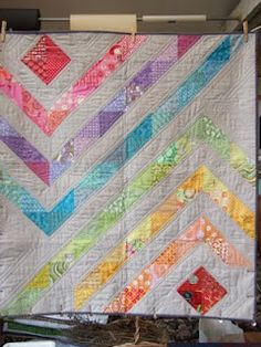 A nice little quilt with a soft and muted rainbow of interlocking scraps.