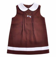 """Vestido para Bebe Niña confeccionado en algodón 100%, """"Piquet"""" en color marron. Cuello redondo en color blanco y sin mangas. Detalle en la parte superior con un lacito en gros color marron con una pluma en nacar y una medallita con el EPK grabado. Una cinta blanca en la parte baja del Vestido. Se abotona en la espalda."""