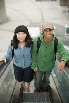 hetero couple riding escalator
