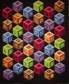 Elisa Lawrance chose brilliant Southwest batiks for this open tumbling block pattern. Thanks to the selection of bright batiks, along with a dramatic black background, the boxes appear to be lit from within. Minimal quilting in the boxes helped to define and accentuate the cubes.