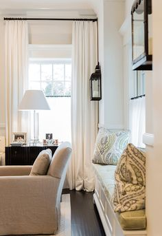 black lantern wall sconces. window upholstered seating. ivory curtains. black curtain rods. neutral colors. off white, ivory, and blue. traditional home décor ideas. café rods.