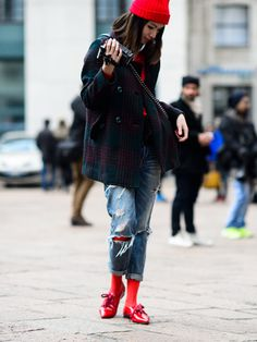 Distressed jeans are paired with red tights, red flats, a red hat, and a dark green coat