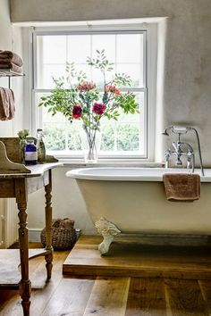 Beautiful turned leg secretary desk used in the bathroom as a freestanding sink or organizing spa supplies. Claw foot bathtub. Fresh flowers. Large window for natural lighting.