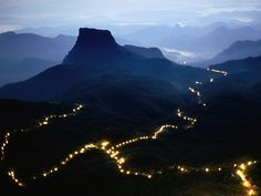 A long line of lights illuminates the path to the summit of Adam's Peak during the Poya Festival in the Central Highlands of Sri Lanka.