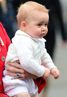 Not tired: Held securely in his mother's arms, the precious eight month old seemed unfazed by the 30 hour flight
