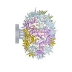 How do you like the idea of having a floral arrangement above the table? The Bloom New lamp family with its elliptical shape and its distinctive original structure covered by sparkling polycarbonate flowers as pure and precious as crystal comes in three different sizes with various functions - hanging, wall or ceiling