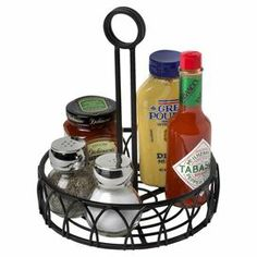 """Set out relish and mustard for afternoon cookouts or honey and jam at Sunday brunch with this steel condiment stand, featuring an openwork design and black finish.  Product: Condiment standConstruction Material: SteelColor: BlackFeatures:  Easy carryingOrganize and store multiple condiment bottles on table or countertopDimensions: 9"""" H x 7.75"""" Diameter"""