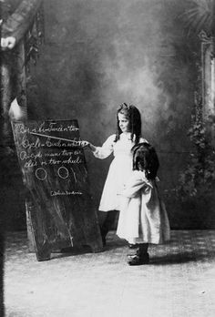 Black and white photo of two little girls standing at a blackboard, one pointing a stick to it, pretending to be a teacher, 1916