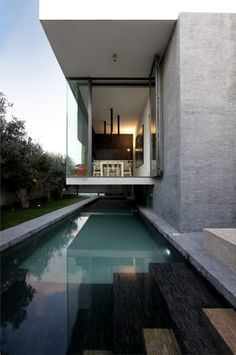 Hanging Home in Malta, by Chris Briffa Architects, photo by David Pisani. The dining room extends into the garden, cantilevered above the pool on a concrete slab.
