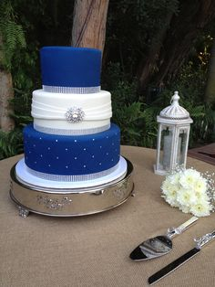 Three tier fondant wedding cake. Royal blue and white, with bling ribbon and a silver broach. http://deliciousartistry.com/