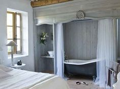 ooooo la la idea - netting over white shower curtain (the clawfoot tub in the bedroom is non too shabby either!)