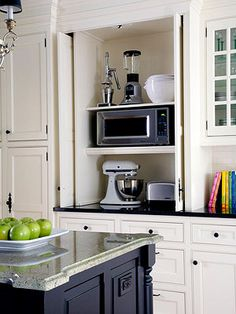 Use a Custom Cabinet like this shown at BHG with retractable doors to keep appliances handy and countertops free!