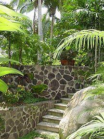Lava rock walls give gardens such a tropical feel. Sloped Backyard, Backyard Ideas, Backyard Decorations, Outdoor Ideas, Garden Ideas, Outdoor Landscaping, Outdoor Gardens, Landscaping Ideas, Rock Wall Gardens