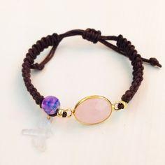 Pulsera hecha con cordón de algodón en color marrón con nudos de macramé.En el centro lleva una piedra preciosa en color rosa, una bola tiedye en tonos rosa y lilas y colgando lleva una pequeña libélula transparente.