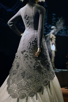 Gorgeous gray sweater dress / coat. Flared with high-low curved hemline layered over ivory sheer. The top part is knit. The bottom lacy openwork is handmade crochet.  Jean Paul Gaultier exhibit at deYoung Museum in San Francisco. Photo by knit cookie, via Flickr
