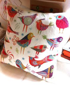 Colorful embroidered folk art birds on a pillow,                              …