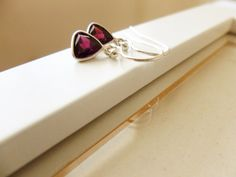 The cute Kim earrings are very on trend with their abstract styling, the 6mm, triangular shaped garnets have been framed in sterling silver and suspended from simple ear hooks, also in silver. | Shop this product here: spreesy.com/poppyandgwynco/10 | Shop all of our products at http://spreesy.com/poppyandgwynco    | Pinterest selling powered by Spreesy.com