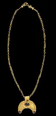 A GREEK GOLD NECKLACE WITH A GOLD AND GARNET LUNATE PENDANT HELLENISTIC PERIOD, 2ND-1ST B.C. figure-8 loop-in-loop chain, hook-and-loop closure fringed with volutes; the pendant formed of a crescent-shaped sheet with filigree beaded, plain and rope wires, cabochon garnet in a dog-tooth setting bordered by beaded wire, wide strap suspension tube. 17 7/8 in. (45.5 cm.) http://www.christies.com/lotfinder/watches/a-greek-gold-necklace-with-a-gold-4821668-details.aspx